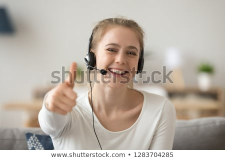joyful office manager talking by headset with microphone stock photo © deandrobot