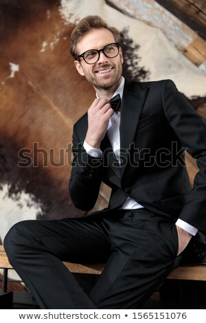 young happy elegant man fixing his bowtie and laughs Stock photo © feedough