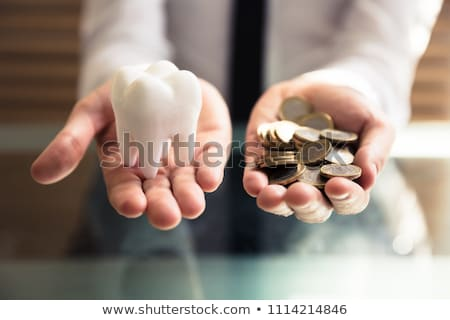 man holding tooth and golden coins stock photo © andreypopov