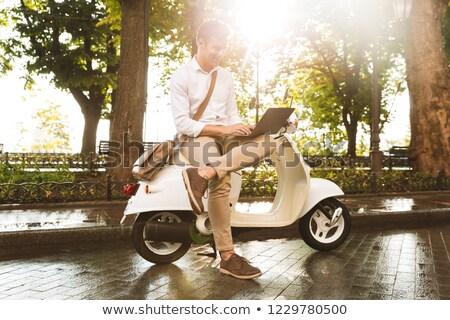 Derűs fiatal üzletember ül motorbicikli kint Stock fotó © deandrobot