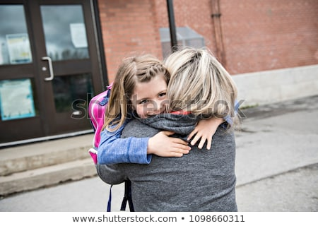 A girl child and his mother hugging outside at school Stock photo © Lopolo