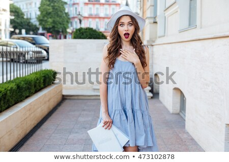 Pretty girl in blue dress surprised looking at camera. stock photo © studiolucky