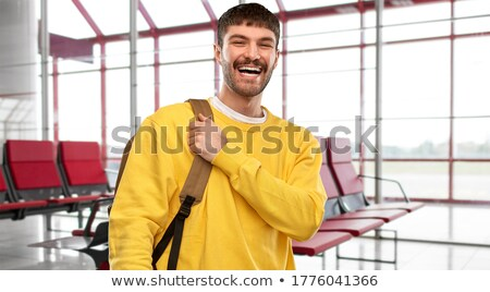 smiling man with backpack over airport terminal Stock photo © dolgachov