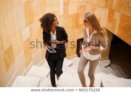 Young successful businesswoman with toothy smile talking to her business partner Stock photo © pressmaster