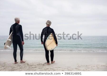 femenino · surfista · pie · tabla · de · surf · playa - foto stock © wavebreak_media