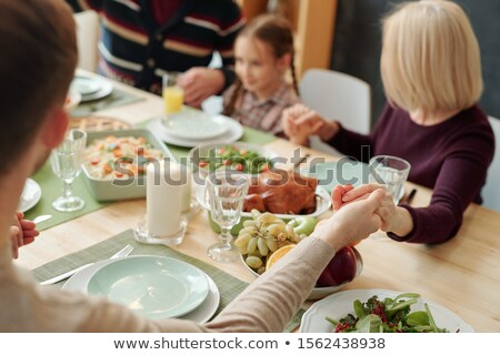 Hands of family held by each other over served festive table during pray Stock photo © pressmaster