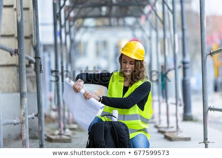 Female architect kneeling with blueprints Stock photo © photography33