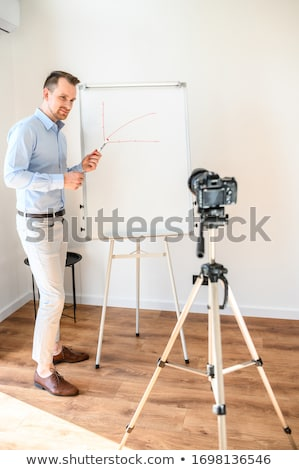 Smiling businessman looking and pointing to white board he is holding Stock photo © wavebreak_media