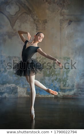 Ballerina in white dress posing on pointe shoes, studio background. stock photo © master1305