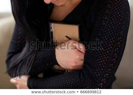 grieving woman with photo frame at funeral day Stock photo © dolgachov