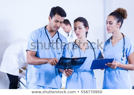 Male and female surgeon having discussion on x-ray report in operation theater Stock photo © wavebreak_media