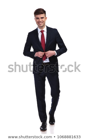 young businessman walking and buttoning his navy suit Stock photo © feedough
