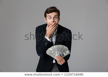 Image of surprised businessman 30s in suit smiling and holding f stock photo © deandrobot