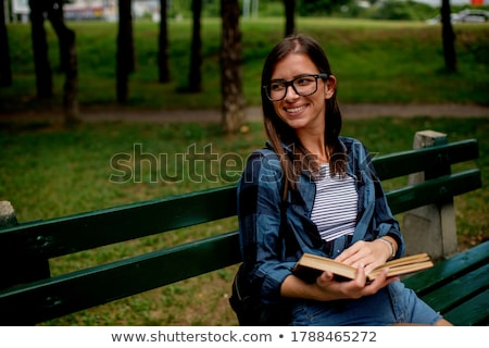 smiling young woman sitting on bench outdoors stock photo © deandrobot