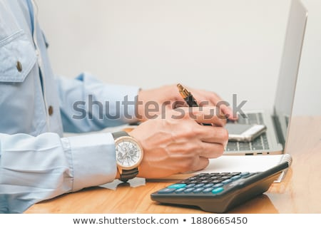 Male hand in a business suit typing financials concept Stock photo © ra2studio