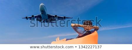 Man tourist have fun on the beach watching the landing planes. Traveling on an airplane concept. Tex Stock photo © galitskaya