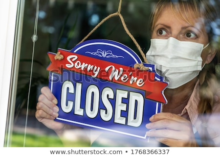 Female Store Owner Wearing Medical Face Mask Turning Sign to Clo Stock photo © feverpitch