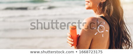 Stock photo: Beautiful young woman in bikini applying suncream