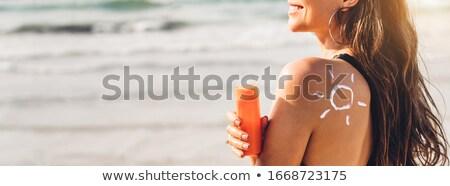 Beautiful young woman in bikini applying suncream Stock photo © AndreyPopov
