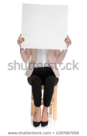 smart casual woman sitting on stool holds advertisement Stock photo © feedough