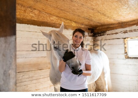 Happy young active woman embracing muzzle of purebred mare in stable Stock photo © pressmaster