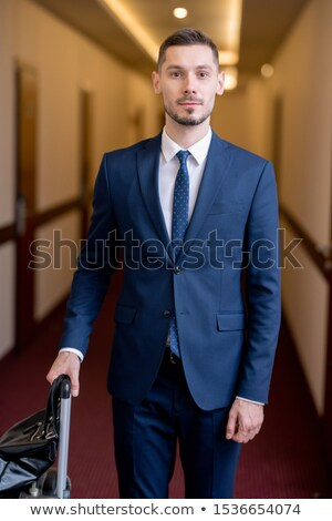 Young successful businessman in formalwear standing in long corridor of hotel Stock photo © pressmaster