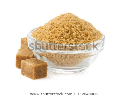 Glass bowl of natural brown sugar cubes on white background. Stock photo © DenisMArt