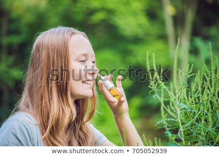 Young woman uses a spray from an allergy because of an allergy to ragweed Stock photo © galitskaya