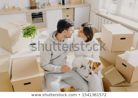 Smiling couple express romantic good feelings to each other, just arrived in new house, pose around  Stock photo © vkstudio