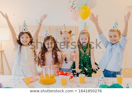 Horizontal shot of happy positive children catch confetti, celebrate birthday together, raise arms,  Stock photo © vkstudio