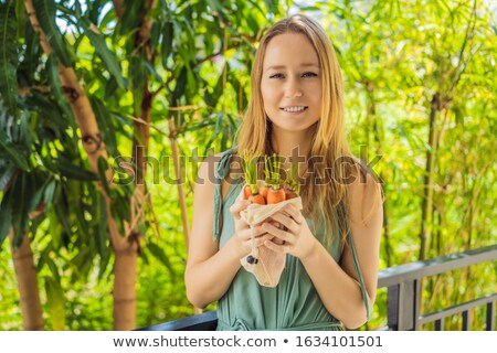 Carrot in a reusable bag in the hands of a young woman. Zero waste concept Stock photo © galitskaya