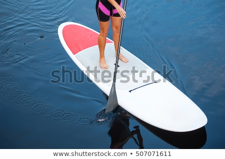 SUP Stand up paddle board woman paddle boarding on lake standing happy on paddleboard on blue water. Stock photo © galitskaya