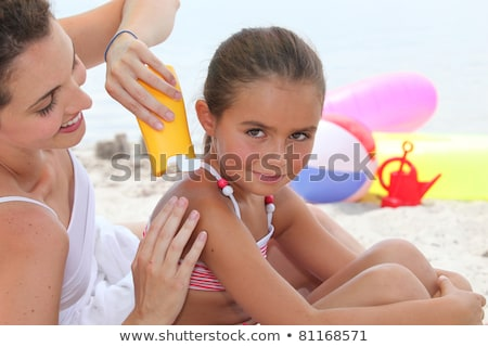 a mother putting sun cream on her daughter's shoulders Stock photo © photography33