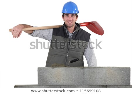 portrait of handsome bricklayer by brickwall holding shovel over his shoulder stock photo © photography33