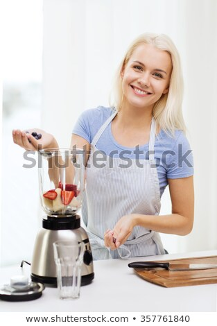 Woman putting strawberries in a blender Stock photo © photography33