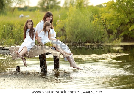 two playing beautiful girls on the background of the river 2 stock photo © acidgrey