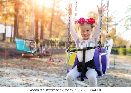 молодые блондинка сидят карусель улице дерево Сток-фото © acidgrey