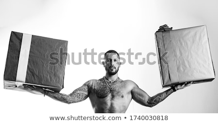 Man with tattooed muscular torso with gift boxes Stock photo © Nejron