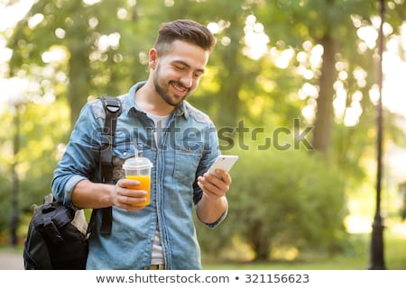 young man with mobile phone in the autumn park stock photo © boggy