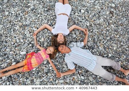 Happy family with little girl lying on stony beach, having joine Stock photo © Paha_L