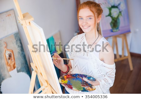 paintbrushes holded by young redhead woman painter in artist workshop stock photo © deandrobot