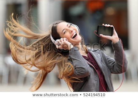 Young smiling beautiful woman listening music with earphones and smartphone Stock photo © deandrobot