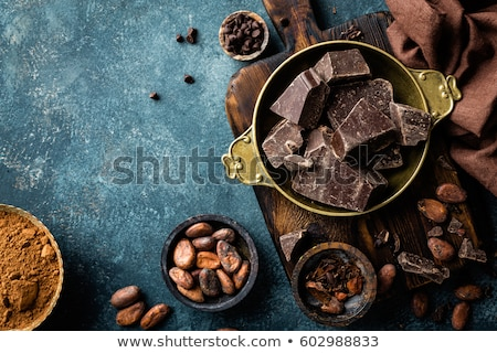 Dark chocolate pieces crushed and cocoa beans, culinary background, top view Stock photo © yelenayemchuk