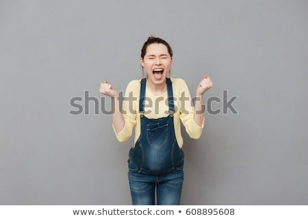 Angry woman posing isolated over white wall background Stock photo © deandrobot