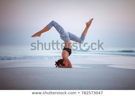 pretty woman practicing yoga on the beach stock photo © vapi