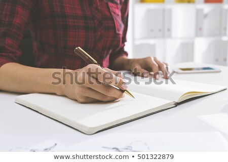 person writing on checkered notebook in office stock photo © andreypopov