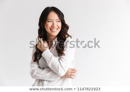 photo of optimistic asian woman with long dark hair looking asid stock photo © deandrobot