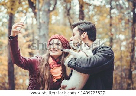 Woman and man with their dog on autumn walk taking a phone selfie Stock photo © Kzenon