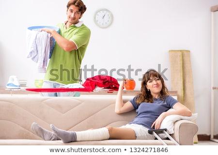 husband helping leg injured wife in housework stock photo © elnur