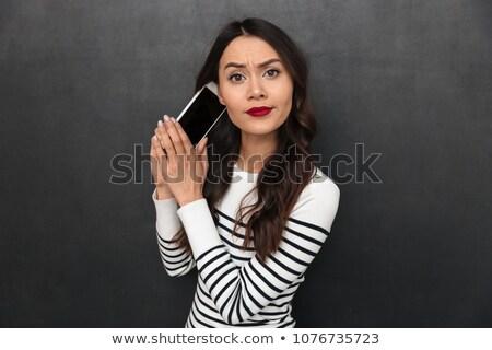 Elégedetlen barna hajú nő pulóver okostelefon néz Stock fotó © deandrobot